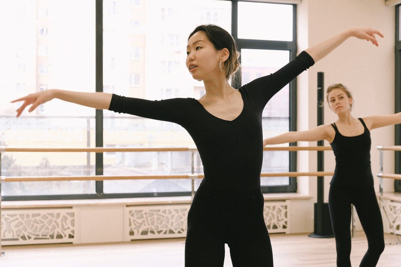 Dance instructor leading a young woman in dance class