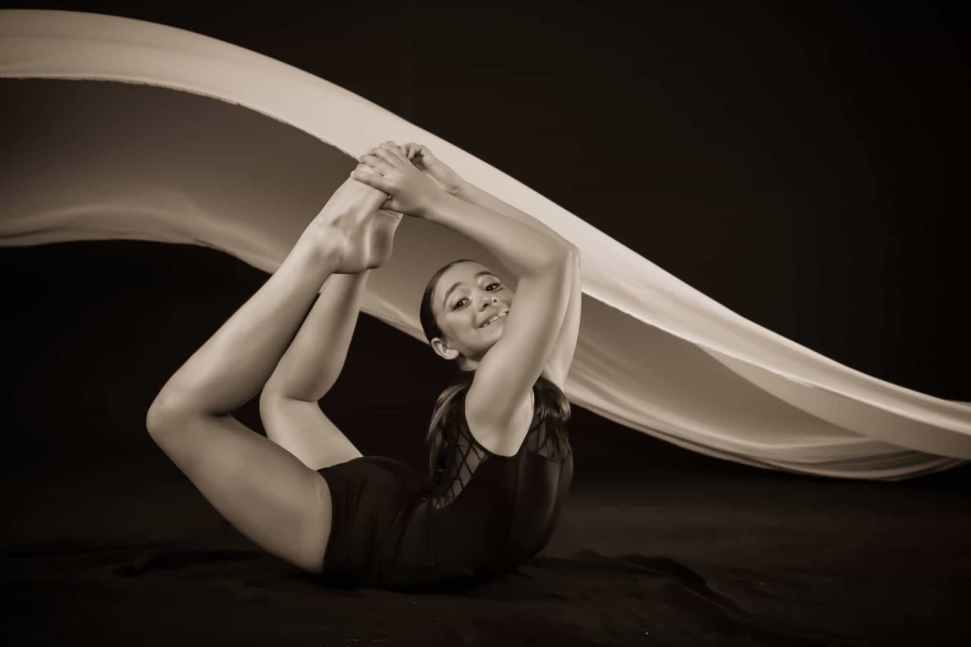 contemporary dancer from oakville dance studio doing a contemporary dance pose with a black background